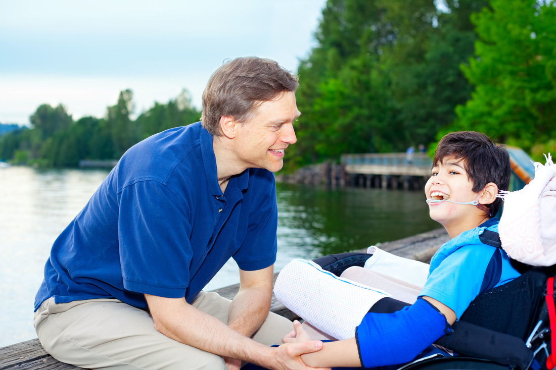 Picture of a young boy receiving assistance by a caregiver near a body of water
