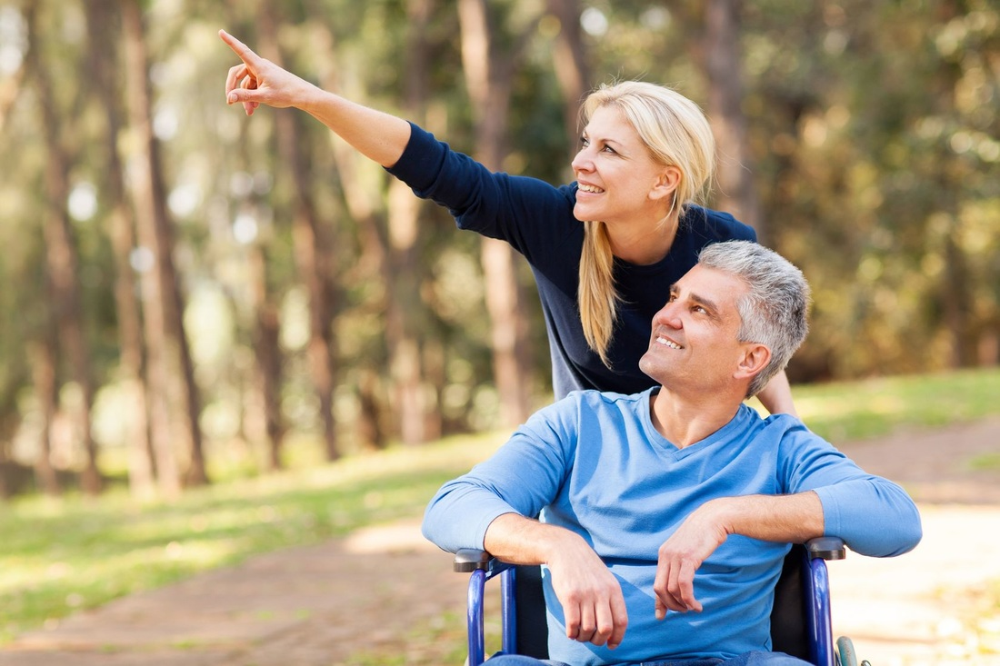 Picture of man in wheelchair with caregiver pointing upward while enjoying a stroll outdoors